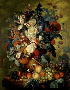 A vase of flowers with fruit