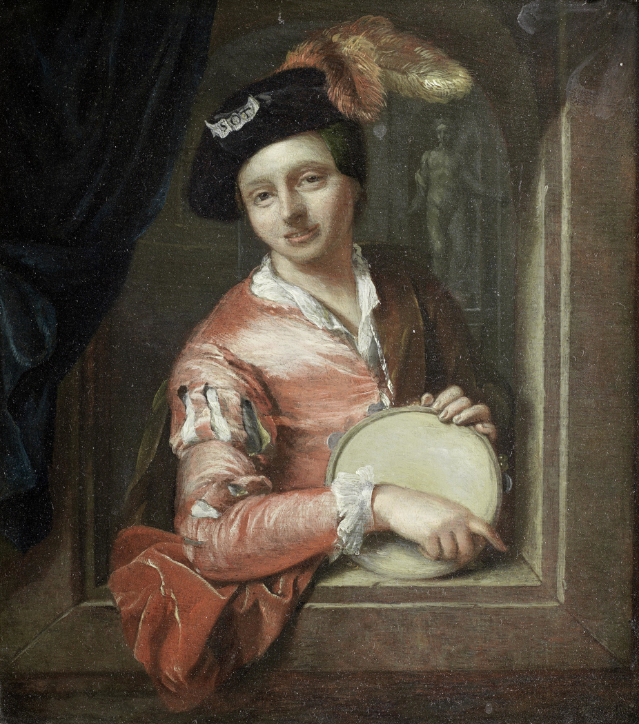A young boy holding a tambourine, at an arch