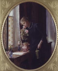 En ung pige, der lugter til en rose