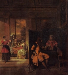 A man and a serving woman behind a screen, with card players beyond