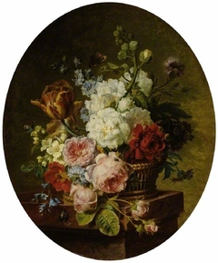Open wicker basket of mixed flowers, including tulip, roses, hareball, hollyhock, poppy, larkspur and auricula on a marble ledge
