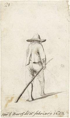 Lopende man met lange stok in zijn hand, van achteren