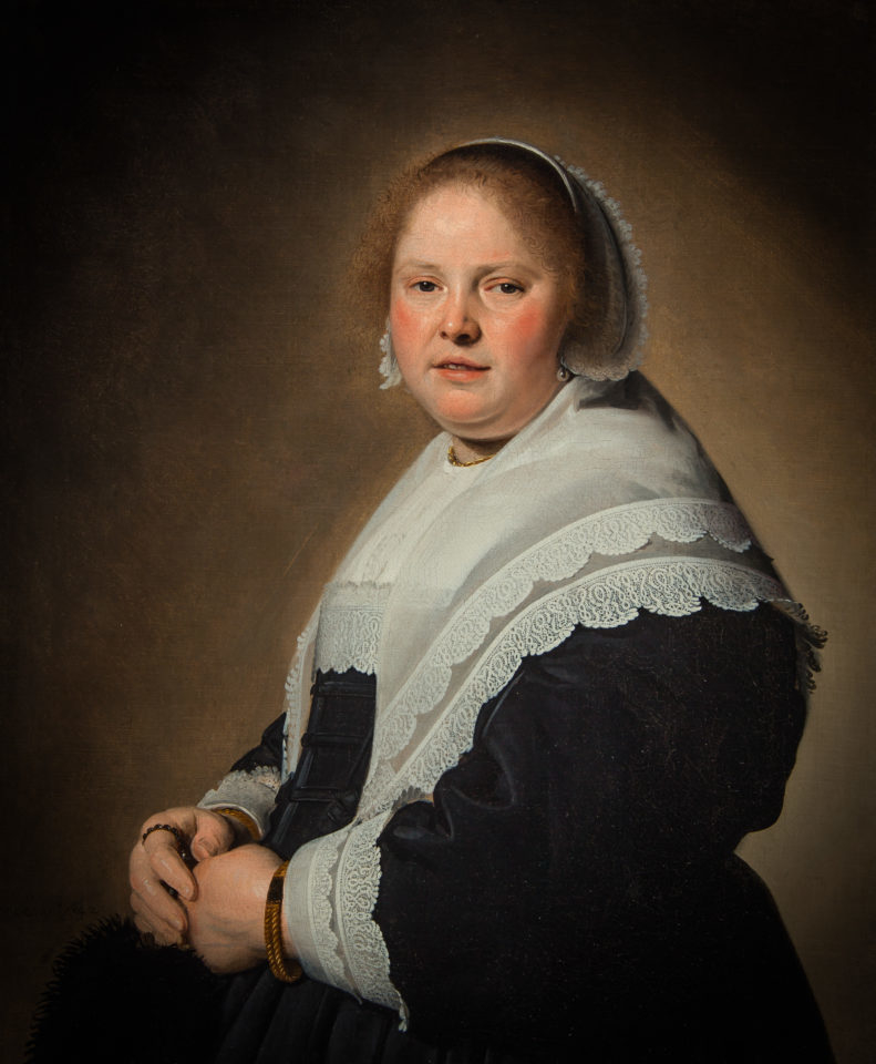 Portrait of an elegant woman in a black dress with a white lace collar