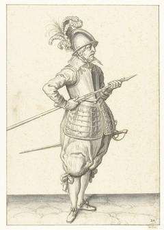Soldaat die zijn spies met beide handen bij zijn rechterzijde draagt, de punt schuin omhoog gericht en vlakbij zijn buik