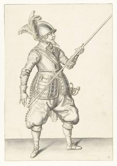 Soldaat die zijn spies met zijn linkerhand bij zijn rechterzijde draagt, de punt schuin omhoog gericht