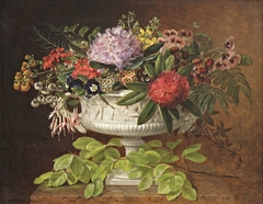 Flowers in a centrepiece on a marble windowsill with a beech branch