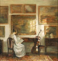 Woman at a table near a cello.