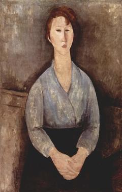 Donna seduta con una camicetta blu